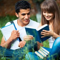 two-students-studying-in-park-on-grass.jpg